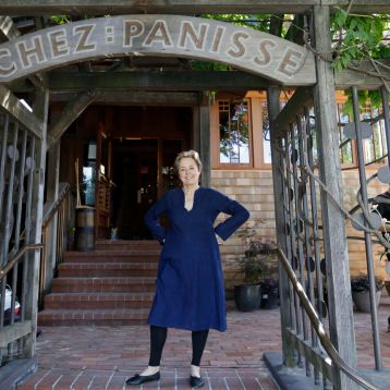 In this photo taken Thursday, June 20, 2013 Alice Waters poses outside the new front entrance to Chez Panisse restaurant in Berkeley, Calif. After a fire in March shut the doors to the famous gourmet restaurant, the eatery is preparing to reopen on Monday, June 24. (AP Photo/Eric Risberg)